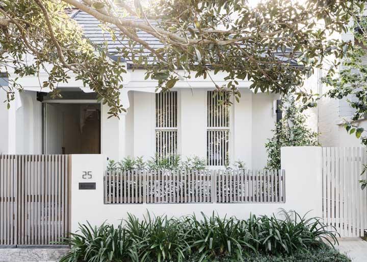 De muro baixo e paredes brancas, essa casa simples traz um belo jardim na entrada