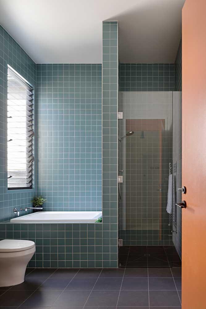 A cerâmica azul colore a região da banheira e contrasta com o piso mais escuro no chão