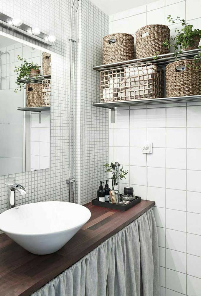 Um banheiro fofo e aconchegante feito com pastilhas cerâmicas brancas contrastadas pelo tom escuro da madeira