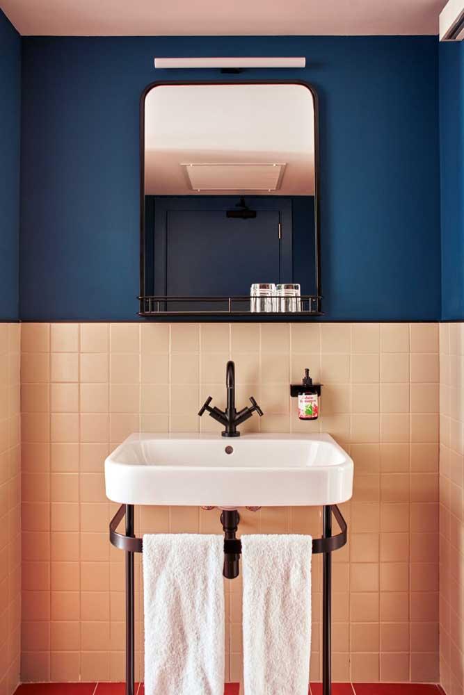 As cores complementares da cerâmica cor de rosa e da parede azul são o grande destaque desse banheiro