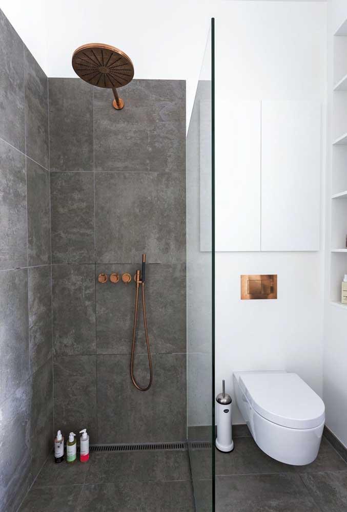 A área do box foi destacada nesse banheiro pequeno com o uso da cerâmica cinza, com textura similar a do cimento queimado