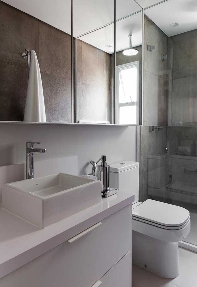 Banheiro pequeno e simples com cerâmica branca no chão e cerâmica cinza na parede