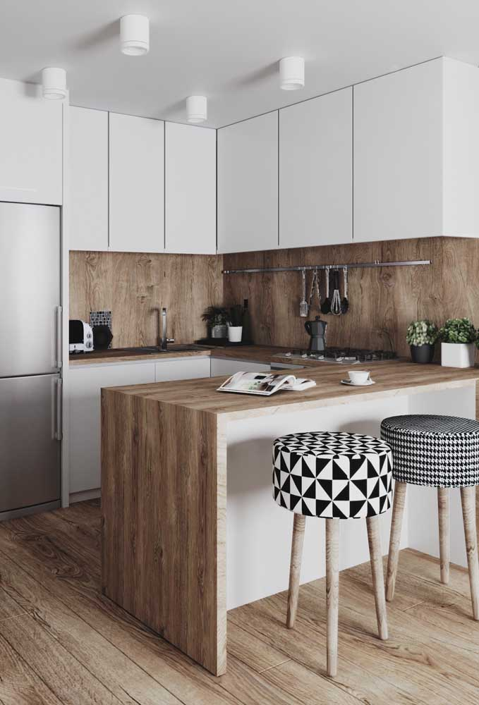Cozinha americana pequena planejada com balcão em madeira e banquetas com estampas modernas