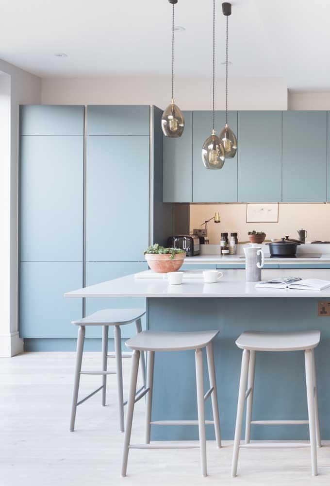 O tom suave de azul marca essa outra cozinha americana pequena planejada com armários sob medida e balcão largo