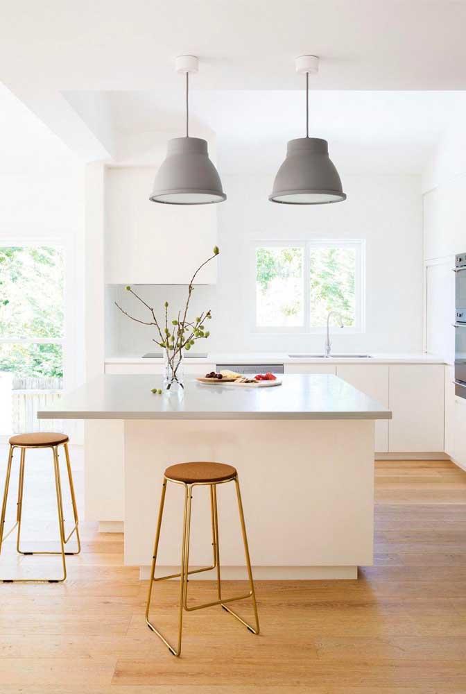 Cozinha americana pequena com ilha; a entrada de luz natural e os tons claros aumentam a sensação de espaço do ambiente