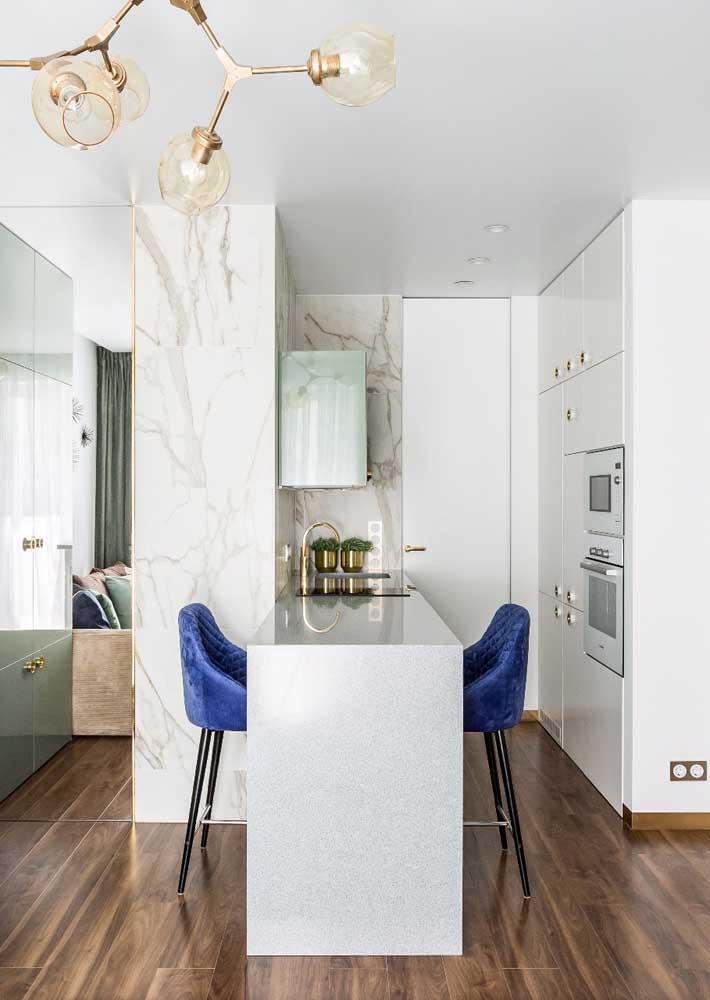 Mesmo pequena, essa cozinha americana conseguiu demonstrar que elegância e sofisticação não se mede em metros quadrados; repare no balcão de mármore e nas banquetas estofadas em azul