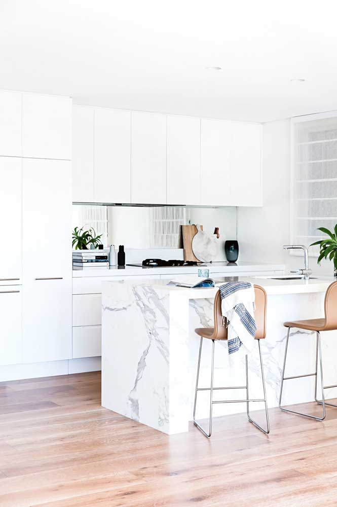 Mais uma inspiração de cozinha americana branca e pequena, com móveis planejados para aproveitar melhor a funcionalidade do ambiente