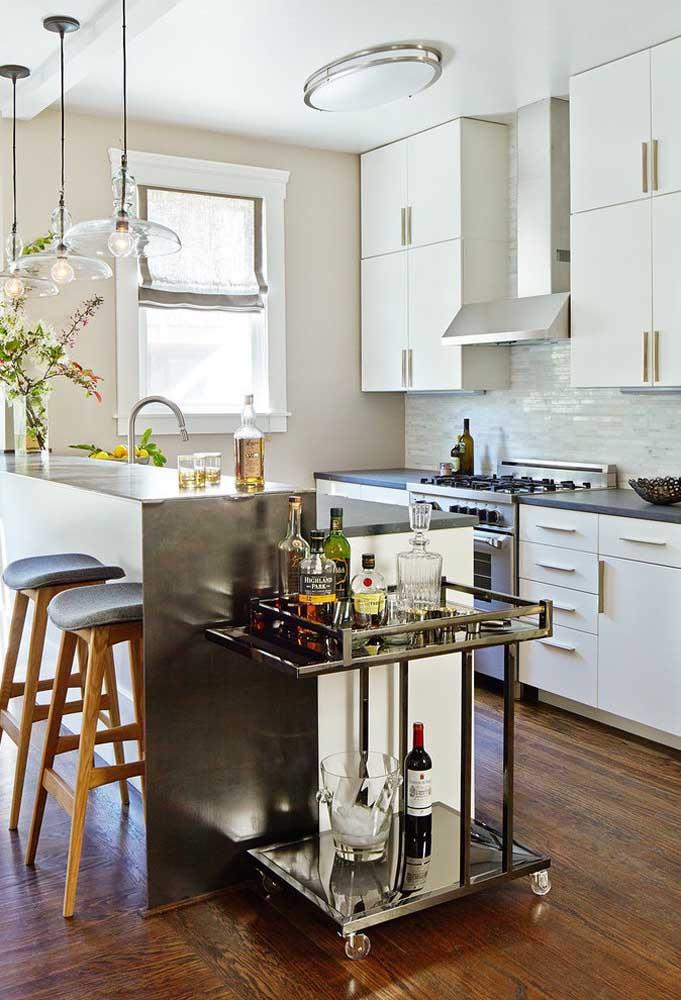 A cozinha americana simples e pequena conta com balcão em alvenaria ao lado do mini bar; destaque para os pendentes