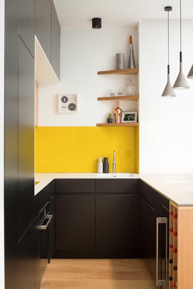 Essa cozinha americana pequena planejada ficou perfeita com as cantoneiras em madeira e a faixa amarela na parede para contrastar com os móveis pretos