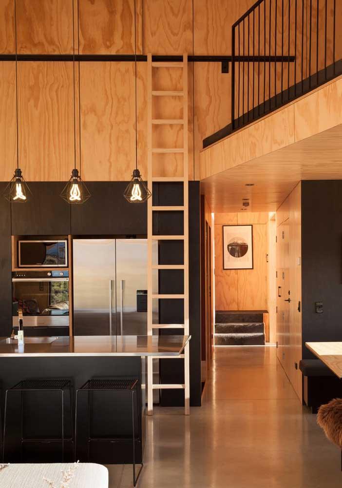 Diferente, essa cozinha americana pequena se integra ao mezanino pela escada no trilho; os móveis pretos se harmonizam com a madeira usada no revestimento da casa