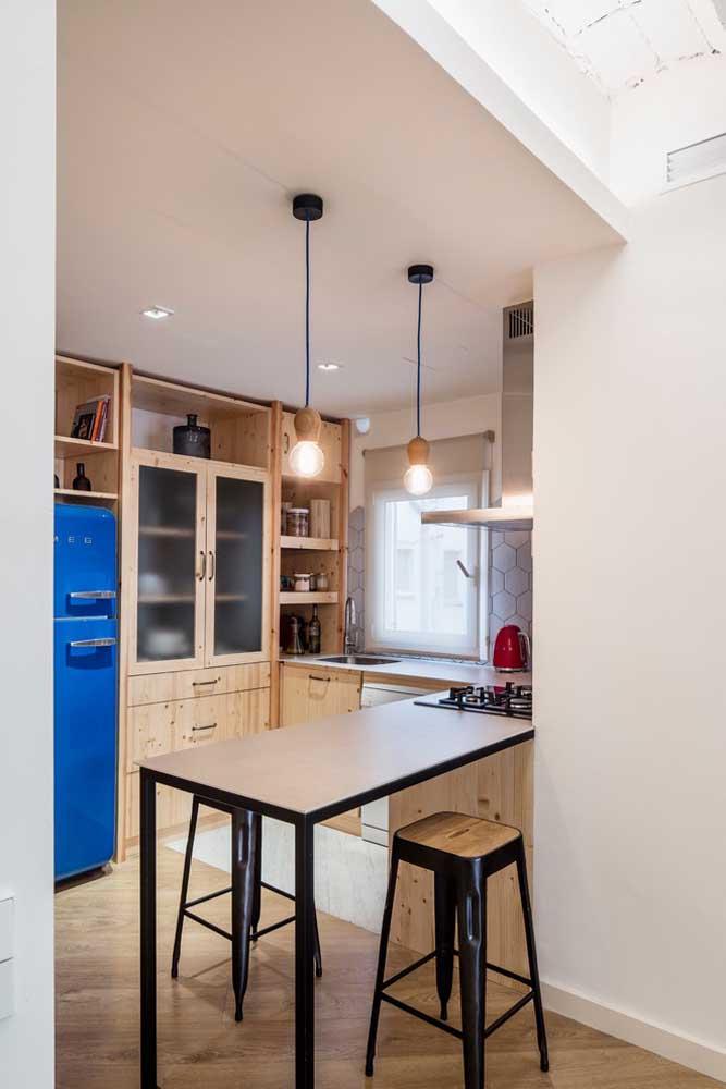 Cozinha americana pequena com móveis em madeira e pendentes industriais para realçar o conceito moderno