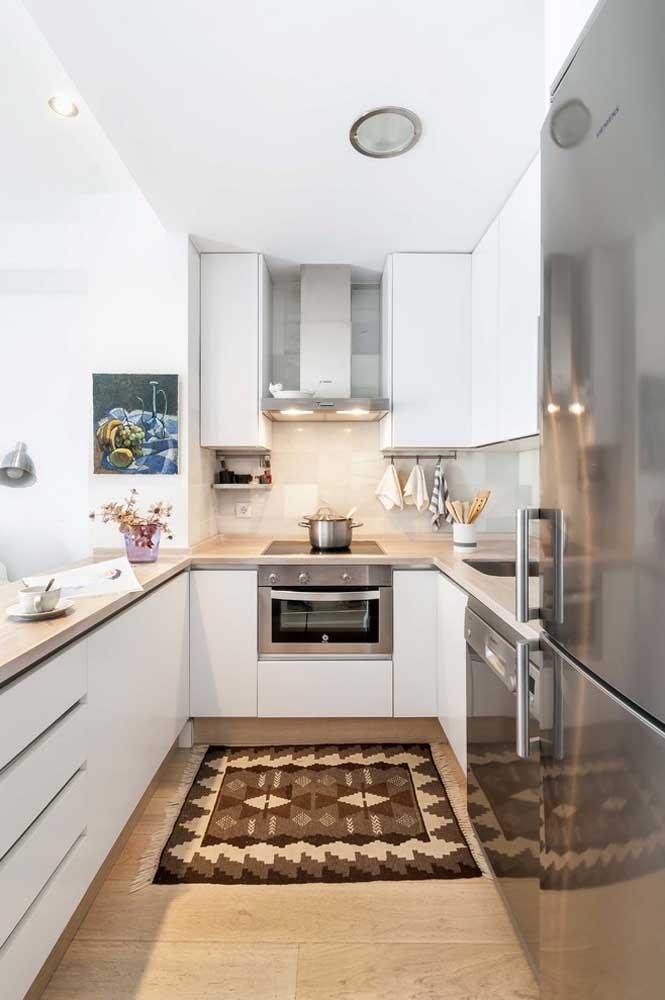 Mais uma inspiração de cozinha americana planejada em U, só que desta vez com armários aéreos e balcão em mármore