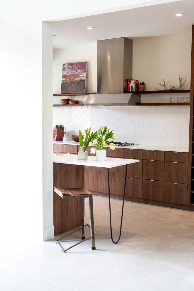 Cozinha americana pequena em madeira; destaque para o balcão com pés grampo