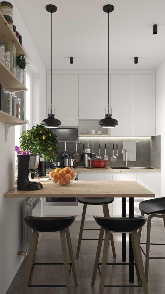 Cozinha americana pequena com mesa em madeira no lugar do balcão