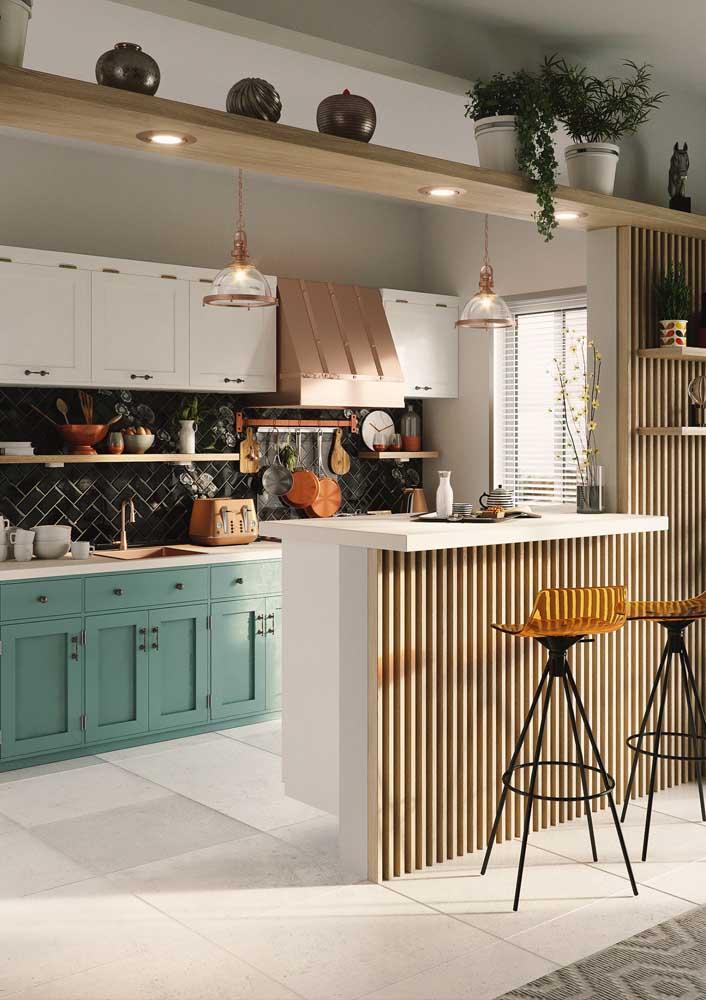 Cozinha americana pequena com armários de marcenaria clássica; as ripas de madeira que formam o balcão e a parede se destacam nesse ambiente
