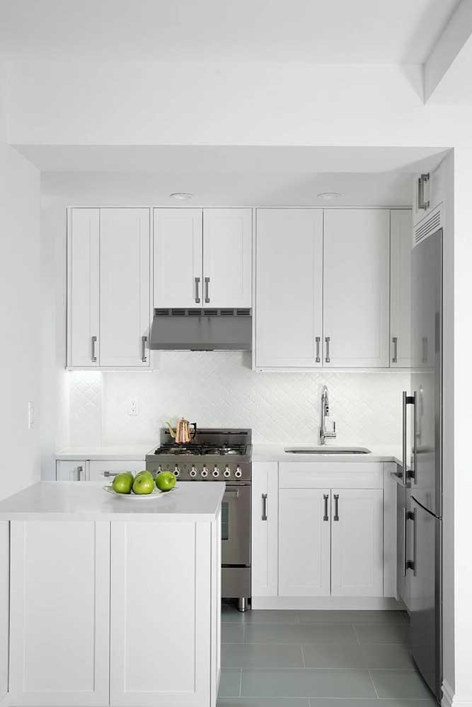 Modelo clássico de cozinha americana pequena: armários com moldura na cor branca e puxadores em ferro