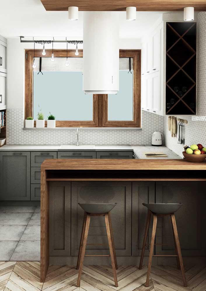 Essa cozinha americana pequena contou com a entrada de luz natural no ambiente, graças a extensa janela sob a pia