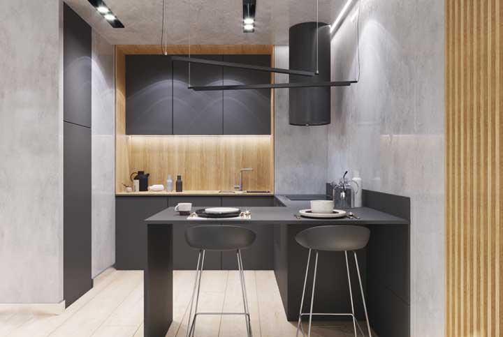 Essa inspiração trouxe uma cozinha americana pequena com iluminação em LED nos armários aéreos e pendentes super criativos sobre o balcão preto