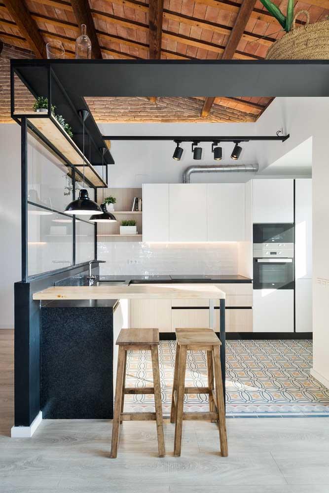 Cozinha americana simples com balcão em estilo industrial; o piso demarca o limite entre cada ambiente