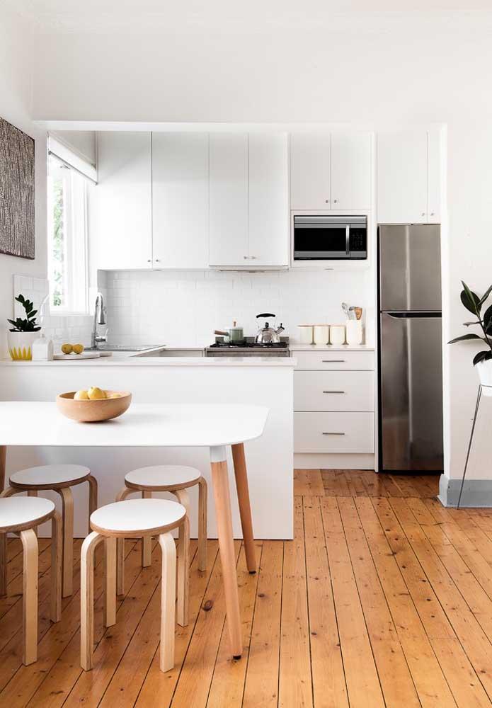 Piso de madeira para contrastar com os móveis brancos da cozinha americana simples