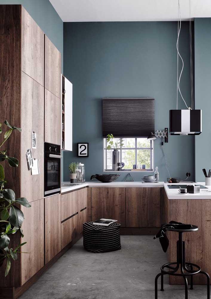 Cozinha americana com pé direito alto valorizada pela pintura em tom de azul fechado; o piso de cimento queimado completa o visual moderno