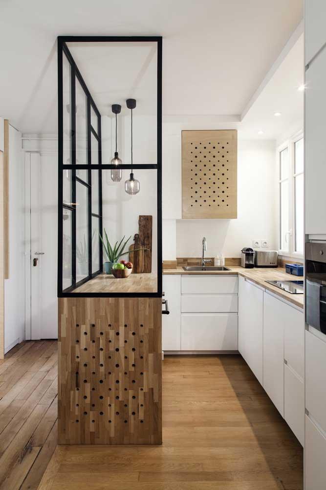 Nessa cozinha americana, logo na entrada da casa, a opção foi instalar uma divisória de vidro sobre o balcão, delimitando os ambientes, mas sem separá-los por completo