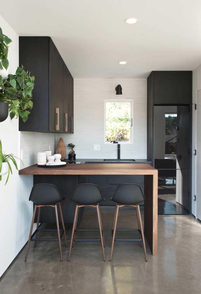 Essa pequena cozinha americana preta ganhou um toque a mais com a presença dos vasos de plantas