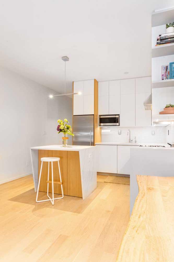 Cozinha americana simples integrada à sala de estar; o pequeno balcão traz praticidade e beleza ao projeto