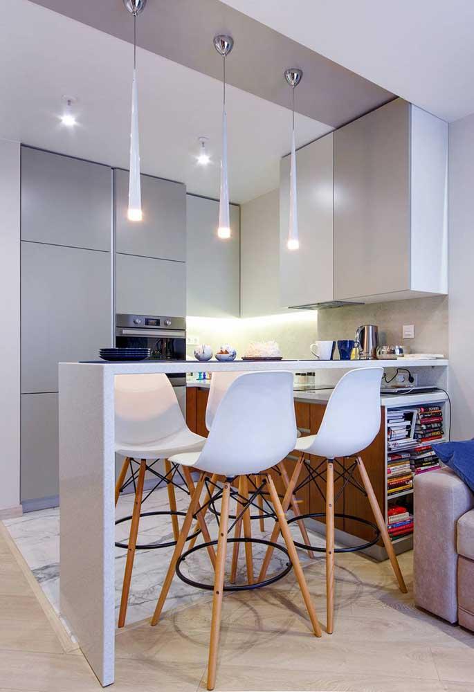 Cozinha americana pequena com balcão; repare que o móvel da cozinha serve como estante de livros para sala