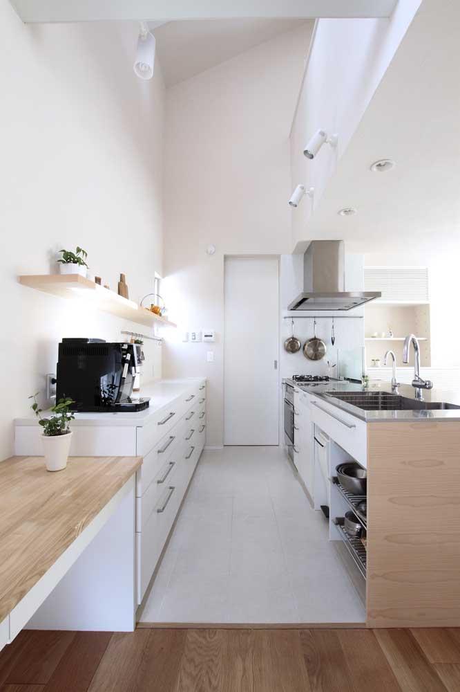 Cozinha americana estilo corredor com pé direito alto; a solução para deixar o ambiente mais amplo foi usar prateleiras ao invés de armários aéreos
