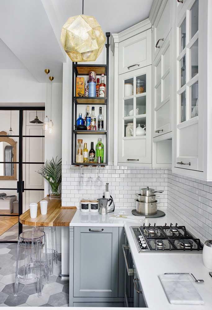 A proposta aqui foi aproveitar os cantos para montar a cozinha americana; os armários de marcenaria clássica são um charme a parte