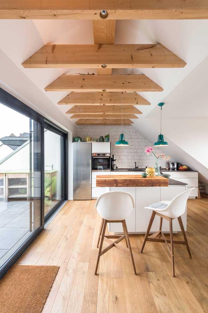 Ampla e espaçosa, essa cozinha americana conta ainda com pé direito alto e abertura de vidro para aumentar a luminosidade