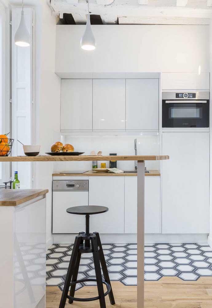 Aqui, o balcão vazado de madeira traz despojamento ao projeto da cozinha americana