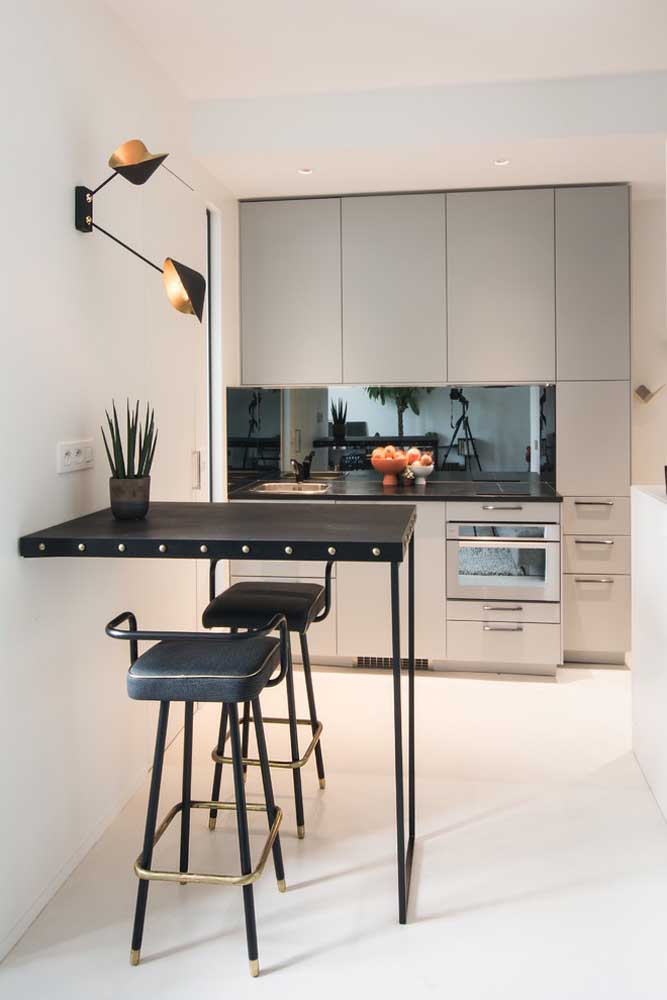Modelo compacto de cozinha americana; todos os móveis e eletros em uma única parede; o balcão preto super estiloso arremata a proposta