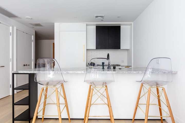 Cozinha americana clean com destaque para as cadeiras altas de acrílico