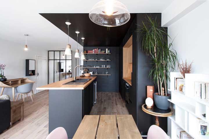 Nessa cozinha americana integrada a sala de estar, a demarcação do ambiente foi feita com a faixa preta pintada no teto