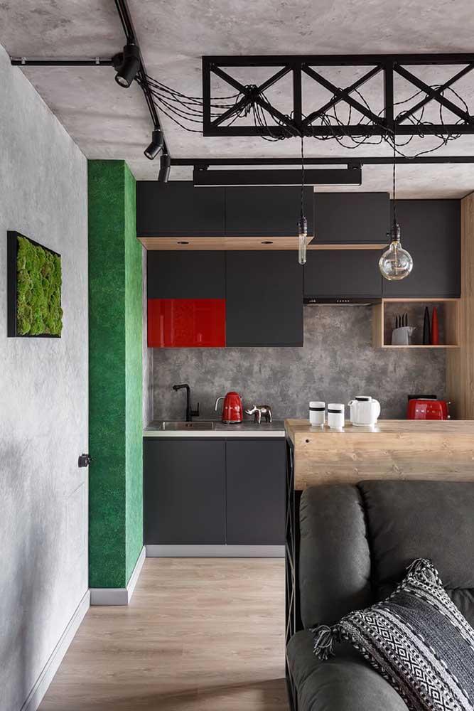 Cozinha americana pequena e simples em estilo industrial; repare que o balcão serve de apoio para encostar o sofá da sala