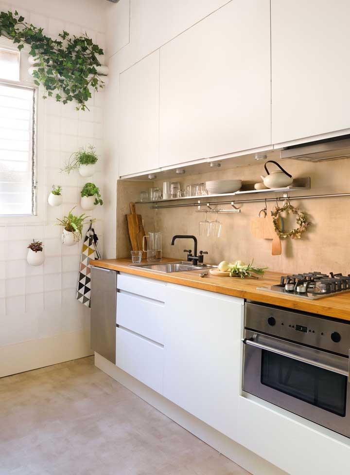Nessa cozinha, a treliça pintada de branco serve como suporte para os vasos