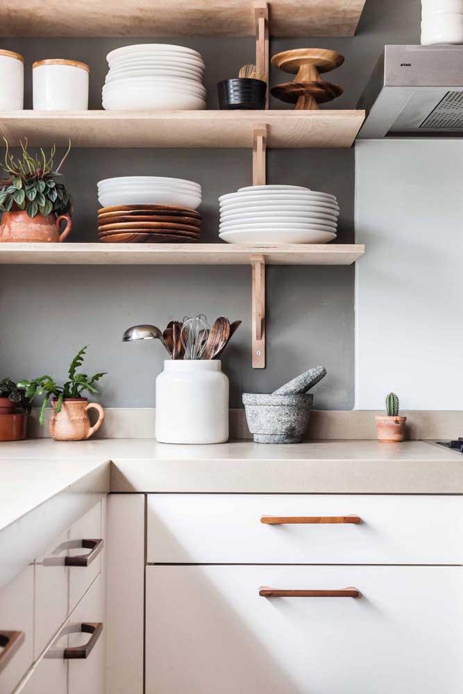 Prateleiras simples de madeira dão o toque de graciosidade para essa cozinha