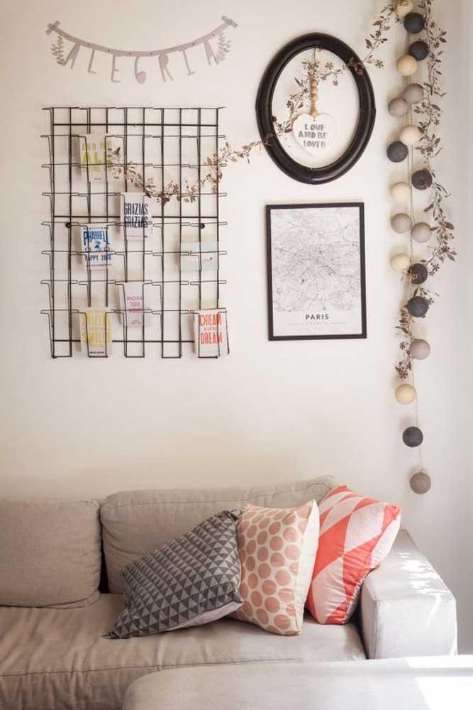 Decoração barata para a sala: a proposta aqui foi usar uma tela aramada como suporte para recados e cartões, além de quadrinhos e outros apetrechos pendurados na parede