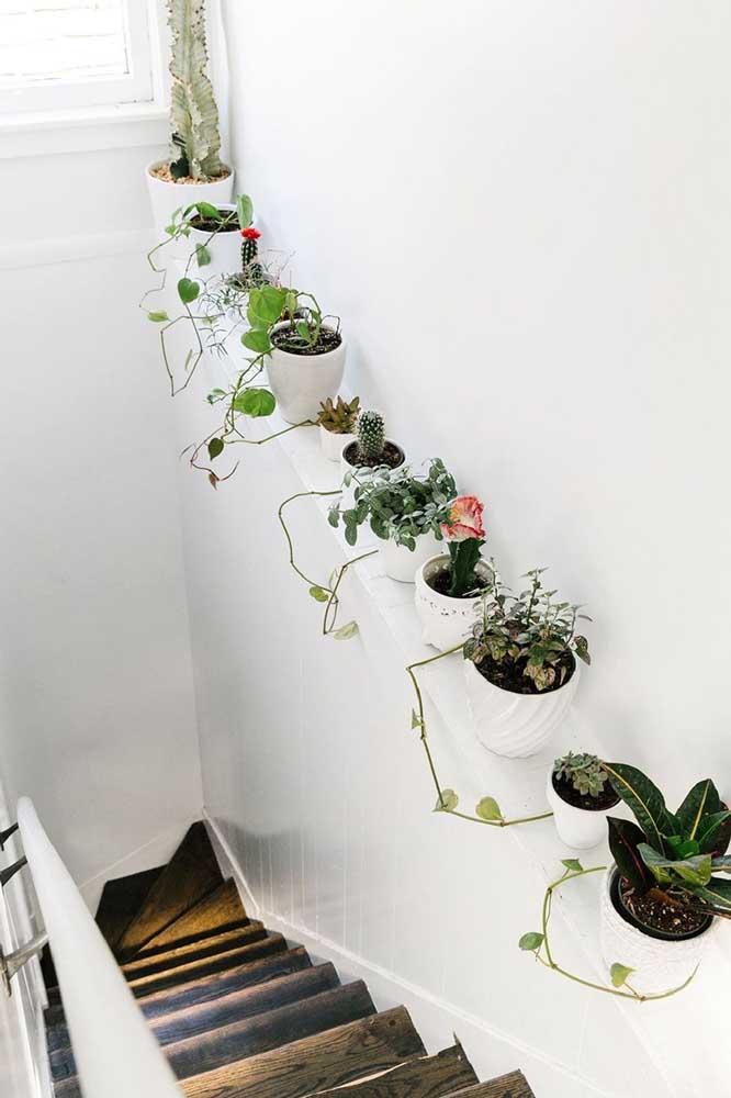 Dê um toque de alegria para a parede da escada usando vasos de plantas