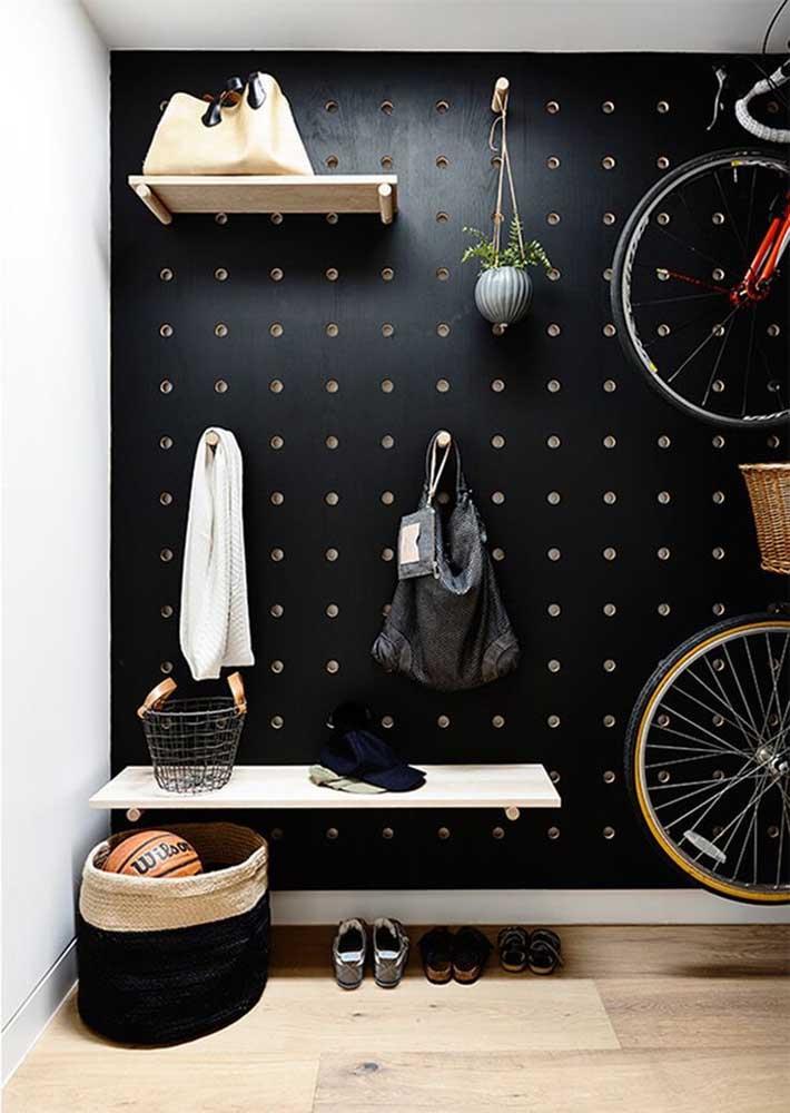 No hall de entrada, mais uma vez ele, o painel com furos; liberdade para você pendurar os objetos que precisar, de casaco à bicicleta