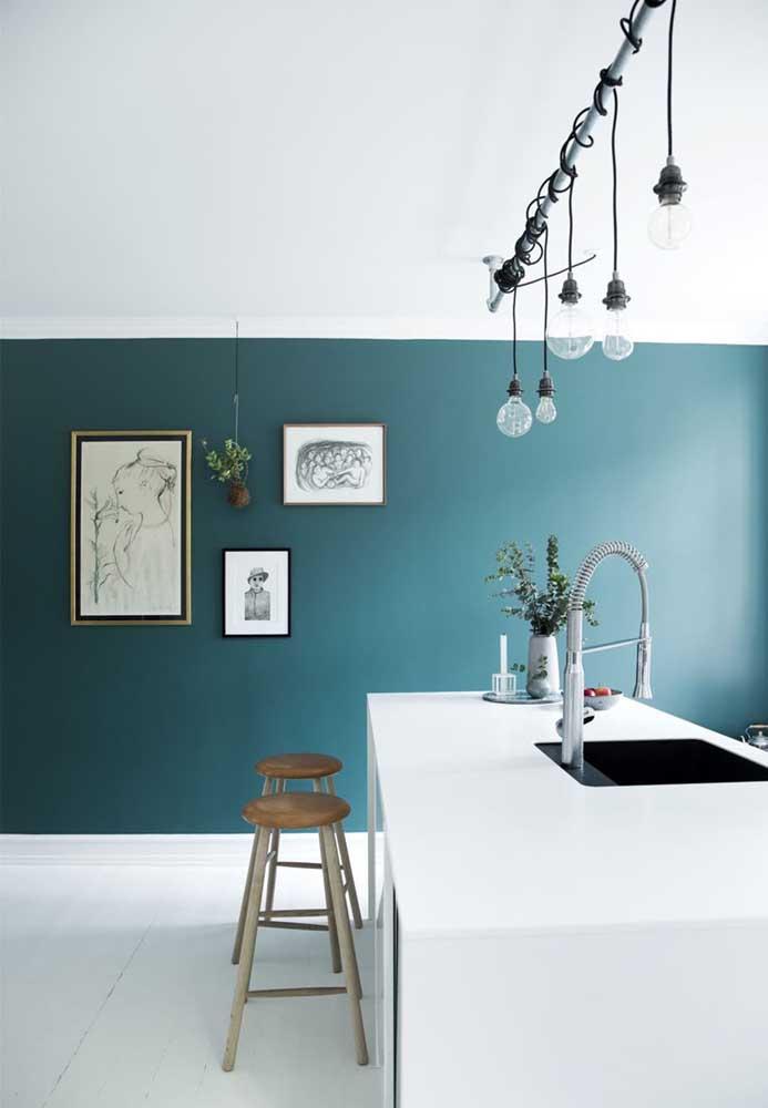 Essa cozinha de estilo clean conta com uma parede meio a meio e uma luminária bem diferente sobre o balcão e que pode ser facilmente reproduzida em casa