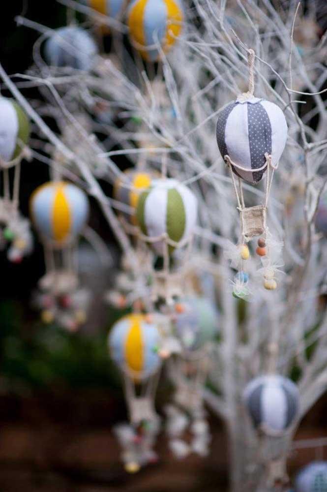 Balões de tecido amarrados no tronco seco de árvore: essa proposta de decoração de batizado pode ser feita por você mesmo