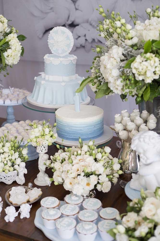 Essa decoração de batizado luxuosa contou com uma mesa para o bolo decorada com muitas flores e doces