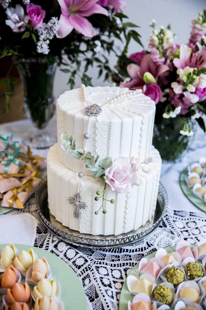 Inspiração pra lá de charmosa para festa de batizado: bolo decorado com renda, flores e terço; ao redor, docinhos finos e muitas flores