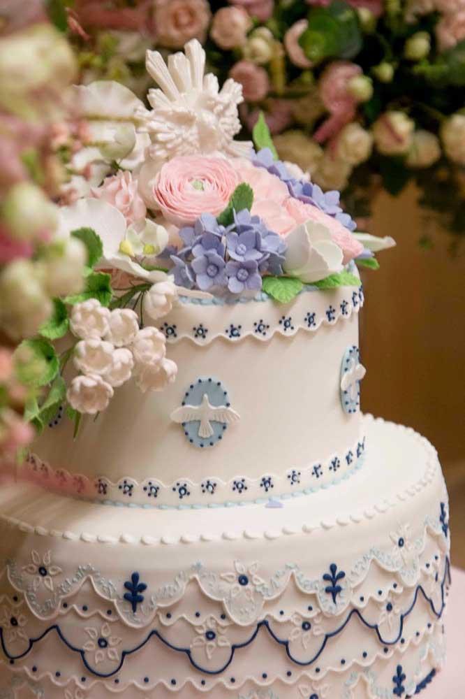 Bolo de batizado em dois andares nas cores branco e azul; as flores no topo completam a decoração