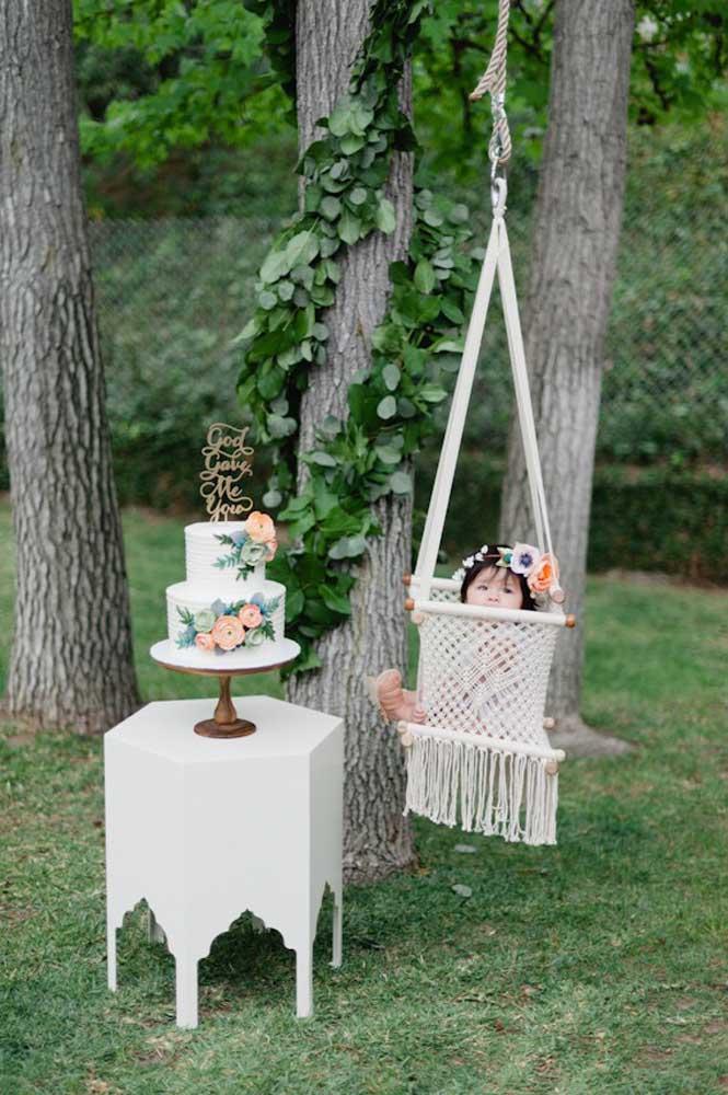 Para a sessão de fotos da festa de batizado: bolo, criança e uma cadeira de balanço em meio a natureza; cenário perfeito