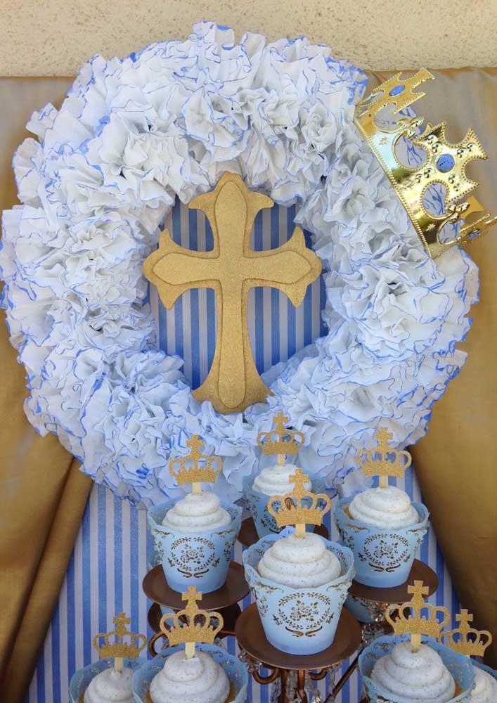 A base dessa decoração de batizado é o papel; repare que o material aparece na guirlanda, na embalagem dos cupcakes e no painel