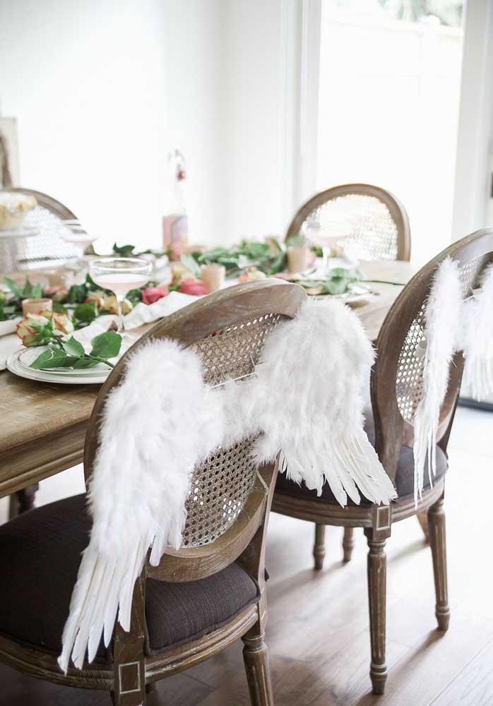 Linda e criativa proposta de decoração de batizado: asas de anjo em cada cadeira
